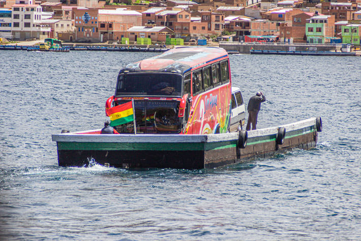 A ferry carries a bus and a van in the strait of Tiquina